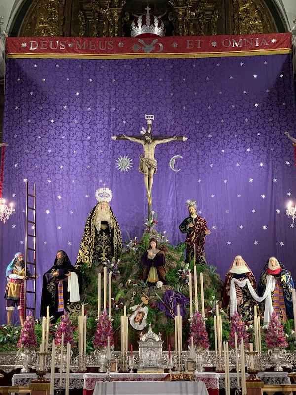 Altar de cuaresma de la Hermandad del Buen con las imágenes del paso de misterio sobre fondo de tela morado con estrellas plateadas.