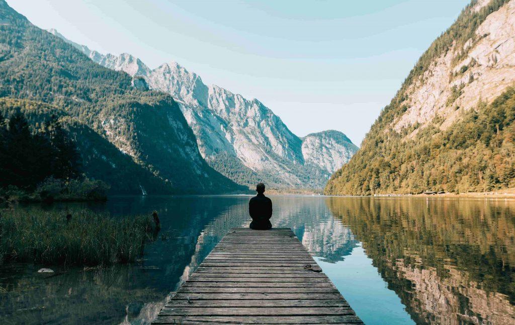 persona meditando frente a un lago y una montaña